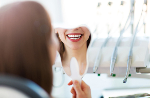 Woman looking at her smile in a mirror at Bryan Hill, DDS in Spokane, WA